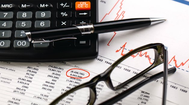 calculator, pen and glasses on top of financial papers