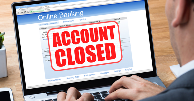 Man Using Online Banking Application On Laptop With Account Closed Message On Screen
