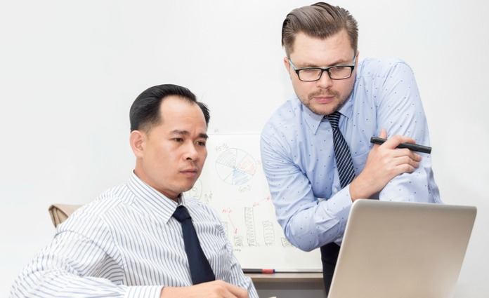 Two office workers looking at laptop screen with puzzled expressions.