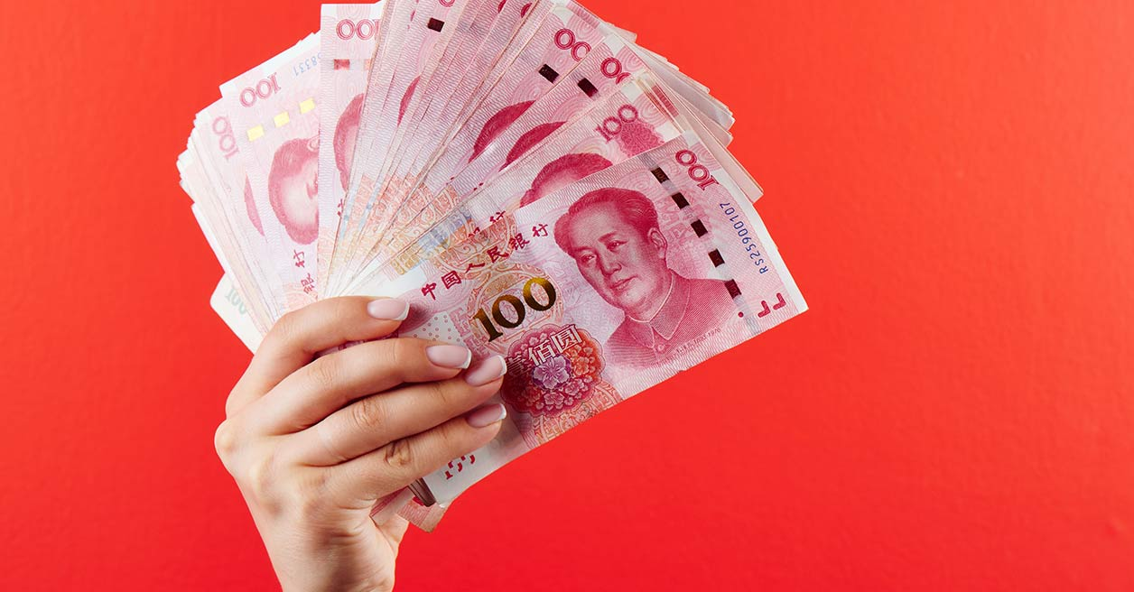 Someone holding up multiple RMB notes